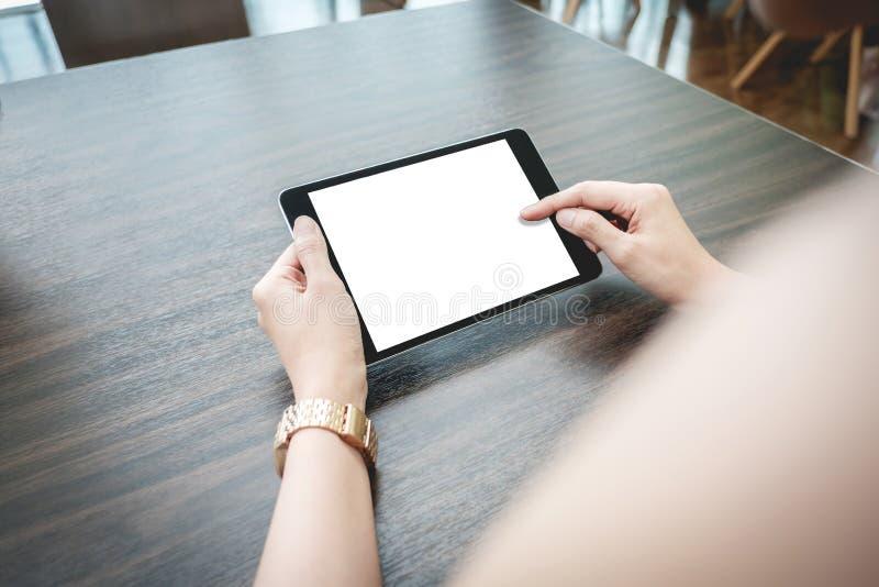 Mujer asiática que usa la PC de la tableta en una tabla de madera imagenes de archivo