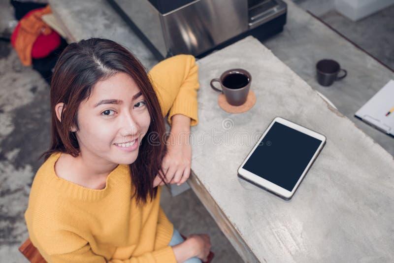 Mujer asiática que usa la tableta en barra del contador del café con la taza de café y fotografía de archivo libre de regalías