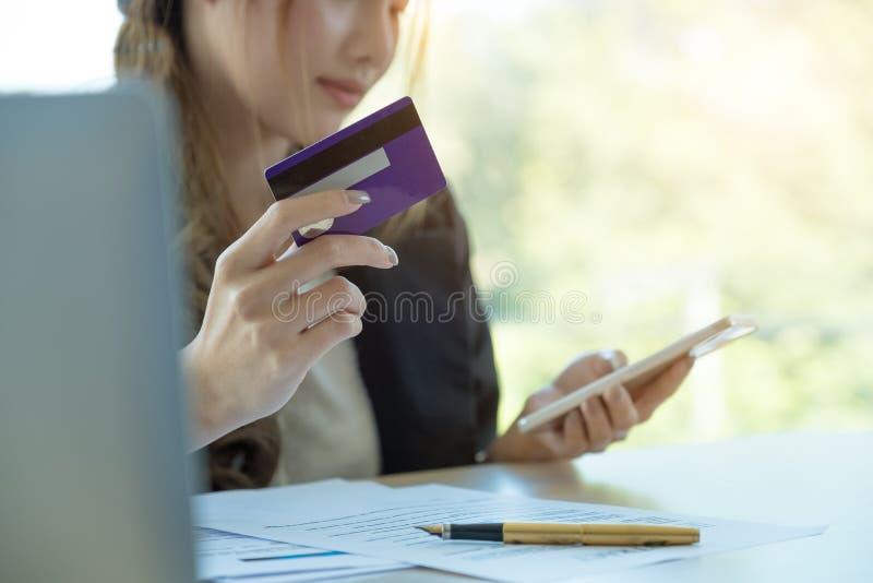 Mujer asiática que usa la tarjeta de crédito que hace compras en línea con smartphone en fotografía de archivo