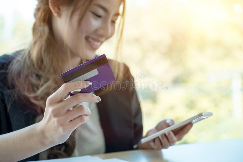 Mujer asiática que usa la tarjeta de crédito que hace compras en línea con smartphone en foto de archivo