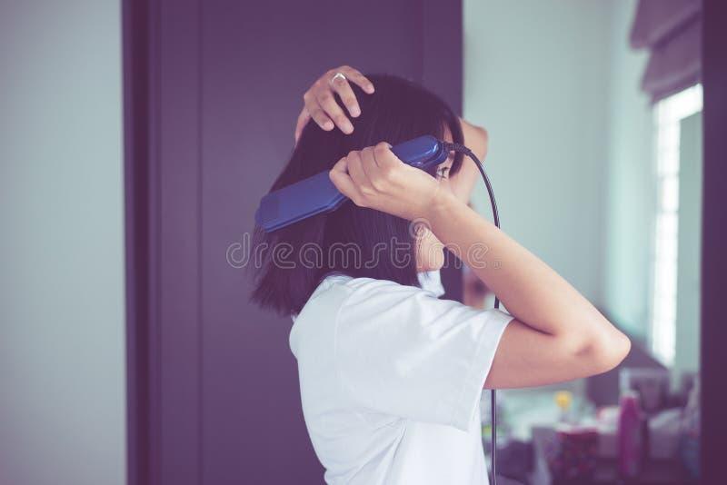 Mujer asiática que usa los hierros del pelo con enderezar el frente del espejo fotografía de archivo libre de regalías