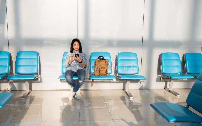 Mujer asiática que usa tiempo móvil de la matanza al esperar salida en el terminal de aeropuerto concepto del recorrido imagenes de archivo