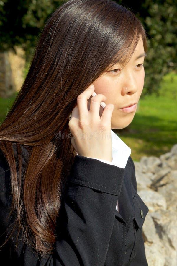 Mujer asiática seria triste en el tiro medio del teléfono fotografía de archivo