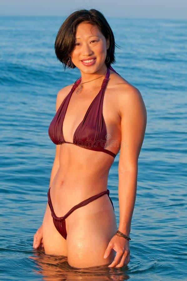 Mujer asiática sonriente atractiva en bikiní imágenes de archivo libres de regalías