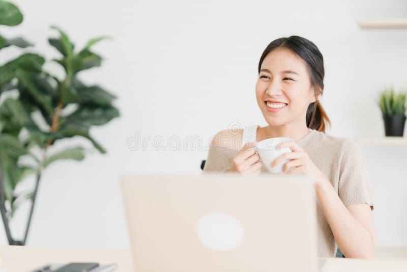 Mujer asiática sonriente de los jóvenes hermosos que trabaja en el ordenador portátil y el café de consumición en sala de estar e imagen de archivo libre de regalías
