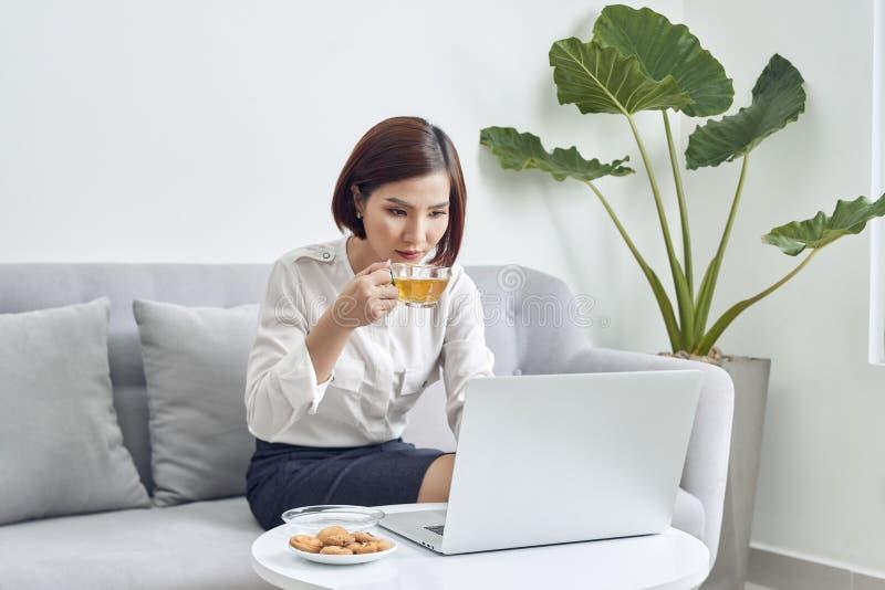 Mujer asiática sonriente de los jóvenes hermosos que trabaja en el ordenador portátil y el café de consumición en sala de estar e imagen de archivo