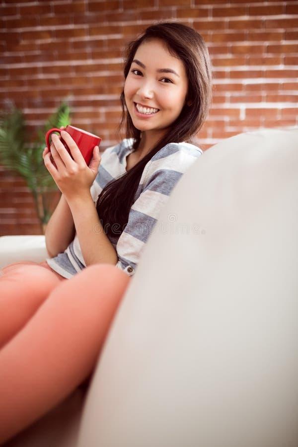 Mujer asiática sonriente en el sofá que tiene bebida caliente foto de archivo libre de regalías