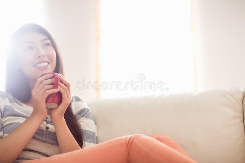 Mujer asiática sonriente en el sofá que tiene bebida caliente imagen de archivo libre de regalías
