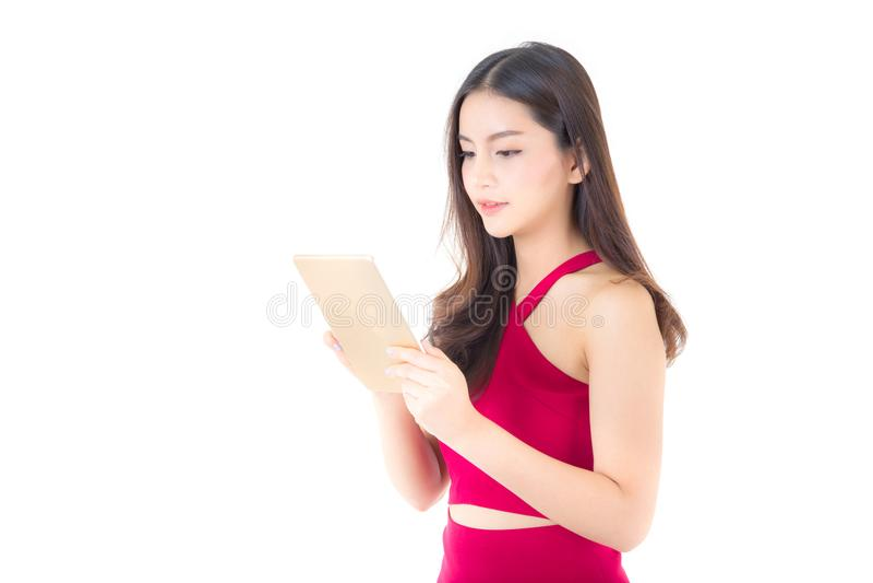Mujer asiática sonriente en el vestido rojo que mira la tableta, mirada de la muchacha y sosteniendo la tableta aislada foto de archivo libre de regalías