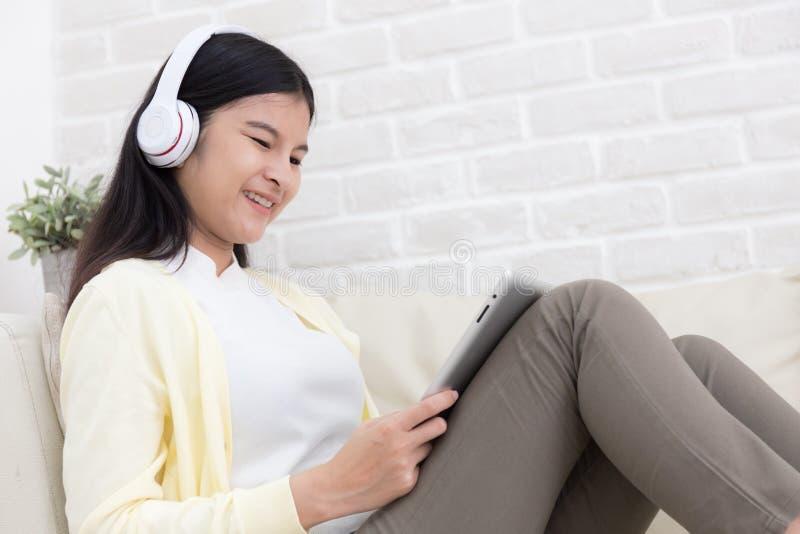 Mujer asiática sonriente que usa la tableta y escuchando la música en el sofá en casa en sala de estar imágenes de archivo libres de regalías
