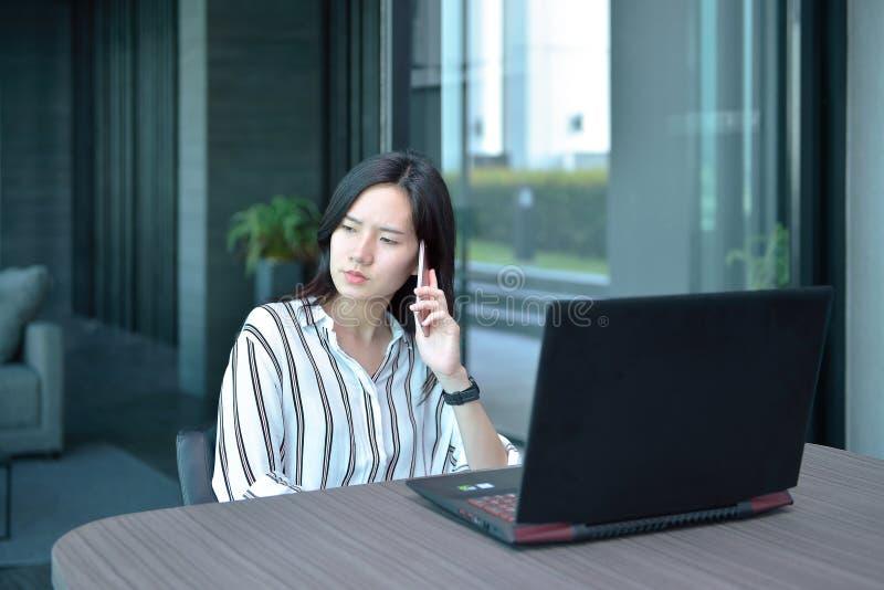 Mujer asiática subrayada del negocio casual que llama por teléfono y que piensa adentro para fotos de archivo libres de regalías