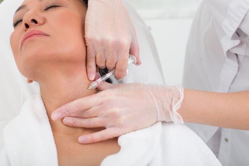 Mujer asiática tensa que toma una inyección en el balneario imagen de archivo