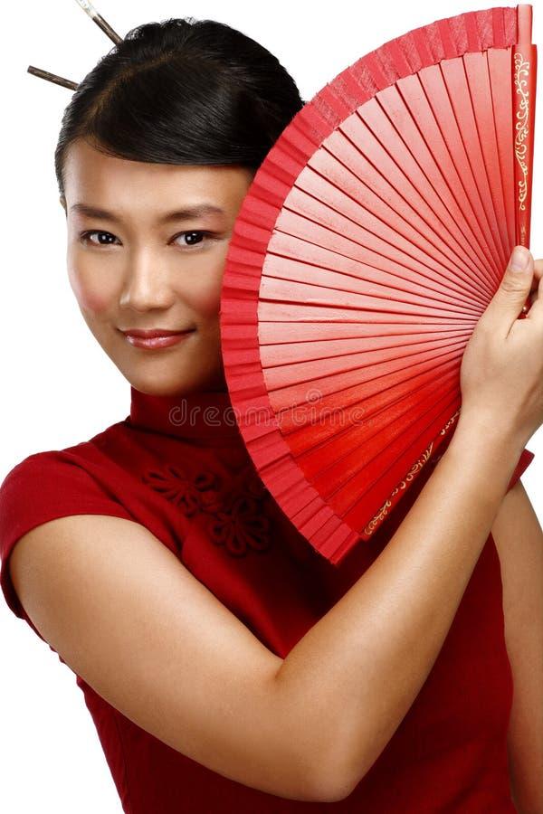 Mujer asiática tradicional que sostiene una fan hermosa roja imagen de archivo