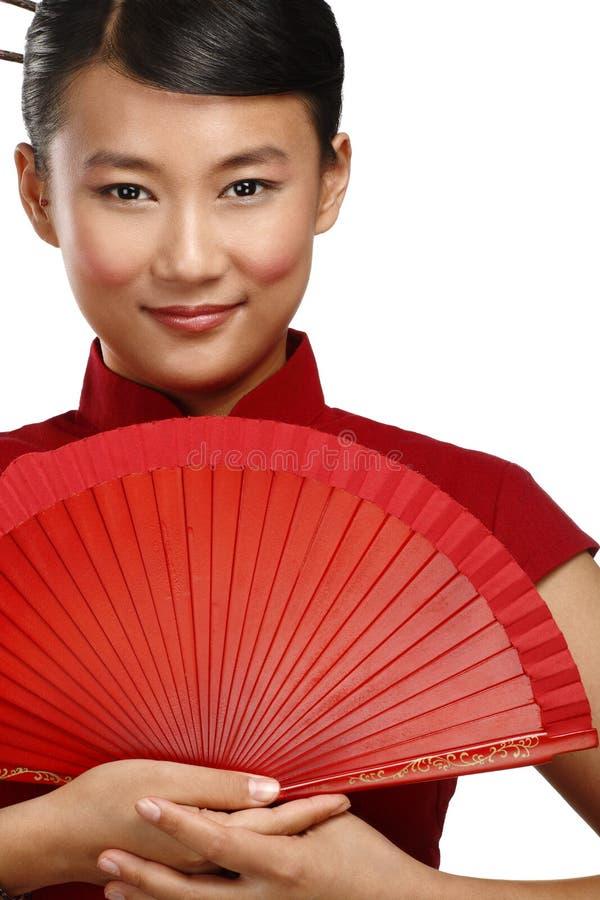 Mujer asiática tradicional que sostiene una fan hermosa roja fotografía de archivo libre de regalías