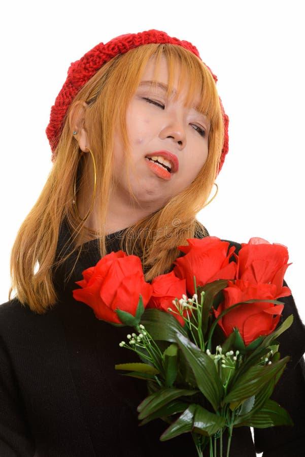 Mujer asiática triste joven que sostiene rosas rojas y que mira lejos foto de archivo libre de regalías
