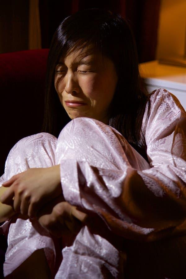 Mujer asiática triste que se sienta en el sofá que llora después de violencia en el hogar imagen de archivo libre de regalías