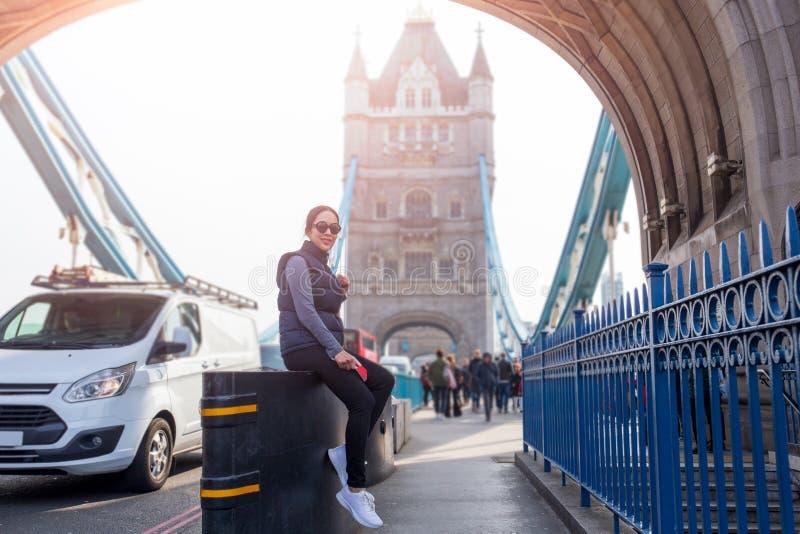Mujer asiática turística que se relaja por el puente Londres de la torre en día de verano imagen de archivo libre de regalías