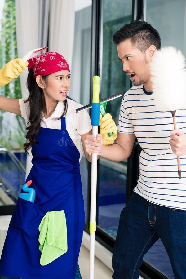 Mujer asiática y hombre que tienen hogar de la limpieza de la diversión fotos de archivo