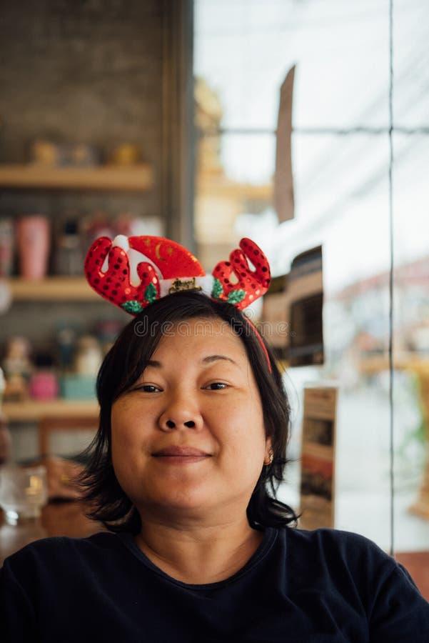 Mujer asiática y sonrisa de la risa de la venda de Papá Noel fotos de archivo libres de regalías