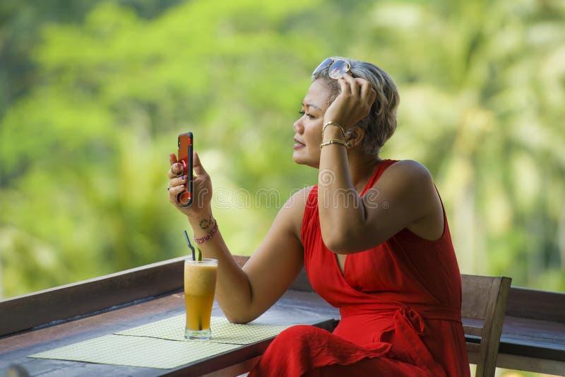 Mujer asi?tica atractiva y relajada 40s o 50s con el pelo gris y el vestido rojo elegante usando medios sociales en el tel?fono m foto de archivo