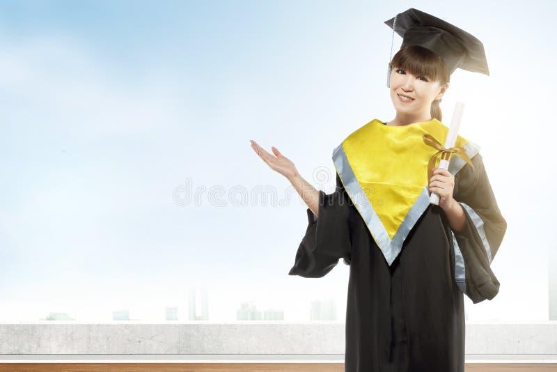 Mujer asi?tica en el sombrero y el diploma del birrete que grad?an de universidad imagenes de archivo