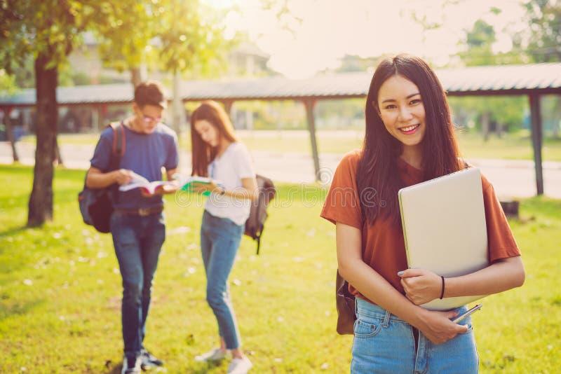 Mujer asi?tica feliz joven que celebra el ordenador port?til y la sonrisa Amistad de la gente y concepto de la tecnolog?a Educaci foto de archivo