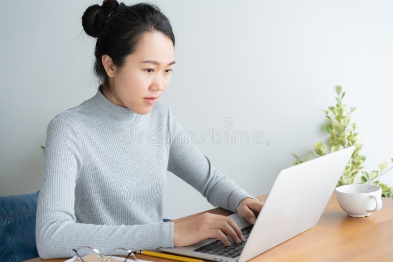 Mujer asi?tica joven que trabaja en el ordenador port?til en el escritorio de Ministerio del Interior fotografía de archivo