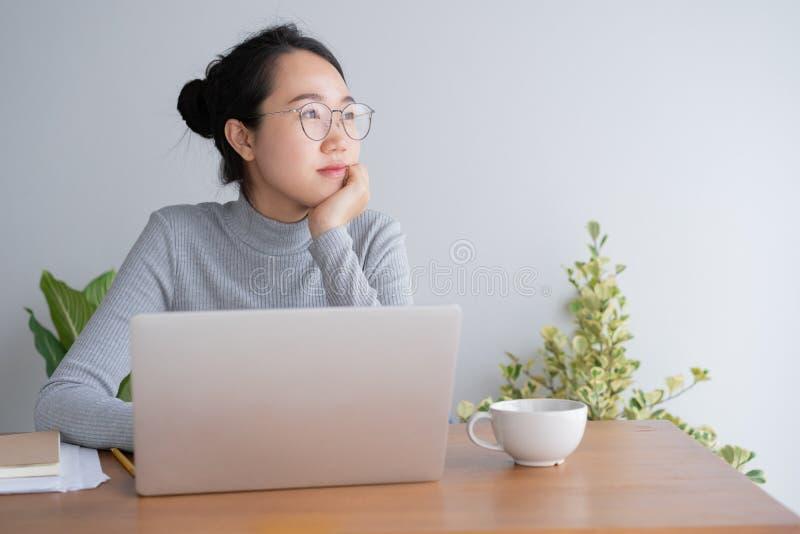 Mujer asi?tica joven que trabaja en el ordenador port?til en el escritorio de Ministerio del Interior Y si?ntese en la barbilla d imagen de archivo libre de regalías