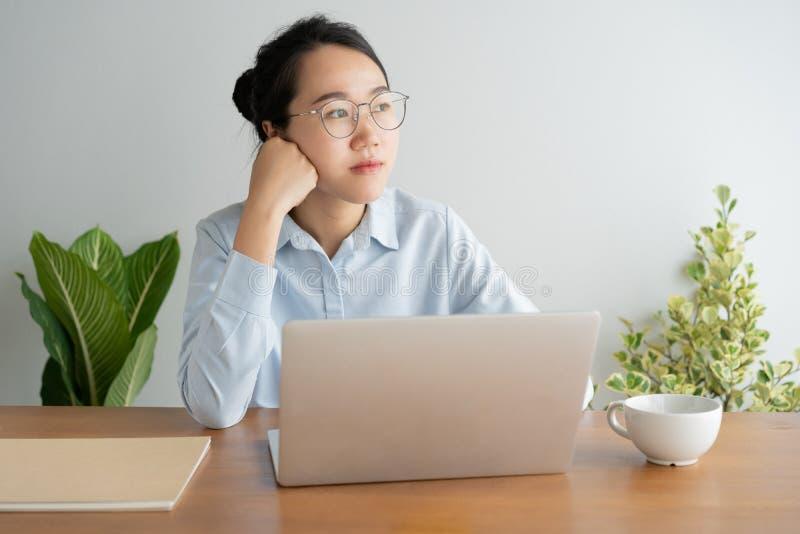 Mujer asi?tica joven que trabaja en el ordenador port?til en el escritorio de Ministerio del Interior Y si?ntese en la barbilla d foto de archivo libre de regalías