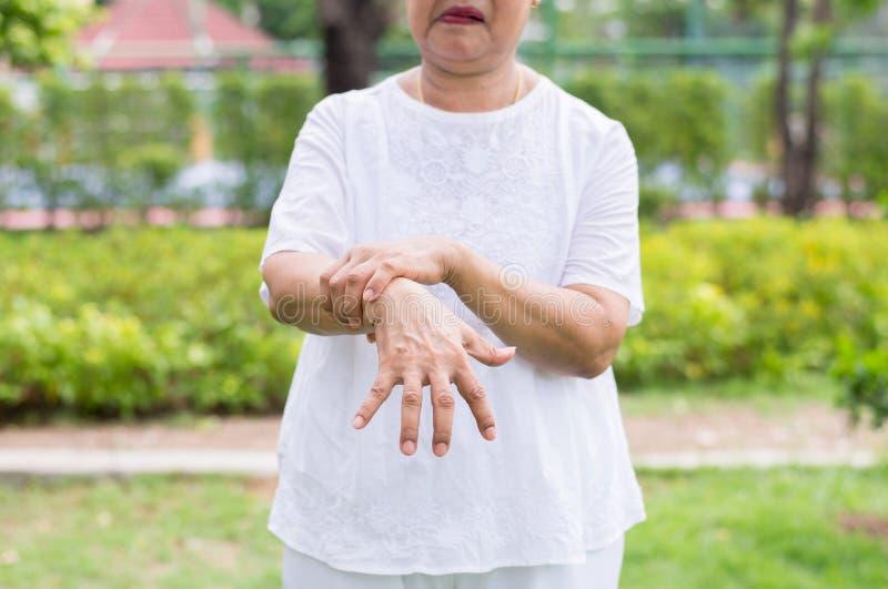 Mujer asi?tica mayor que sufre con los s?ntomas de la enfermedad de Parkinson fotografía de archivo libre de regalías