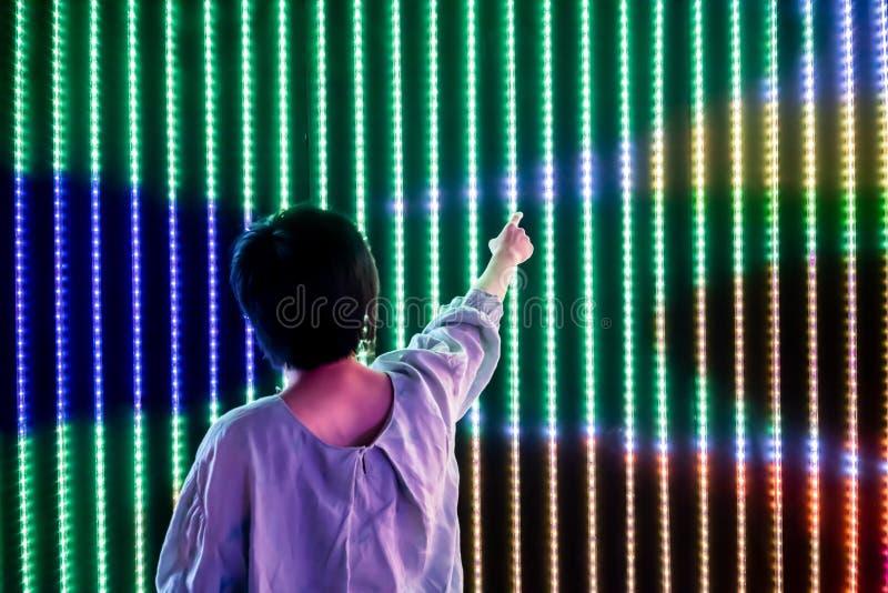 Mujer asi?tica que juega con la pared ligera llevada de la interacci?n fotografía de archivo libre de regalías
