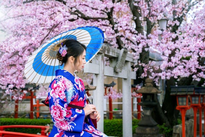 Mujer asi?tica que lleva el kimono y la flor de cerezo tradicionales japoneses en la primavera, templo de Kyoto en Jap?n imágenes de archivo libres de regalías
