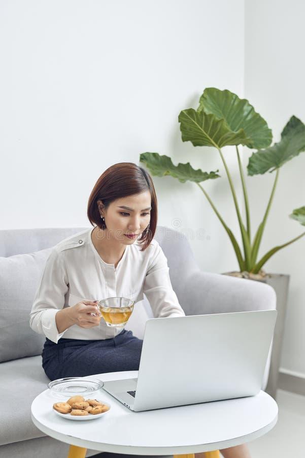 Mujer asi?tica sonriente de los j?venes hermosos que trabaja en el ordenador port?til y el caf? de consumici?n en sala de estar e foto de archivo