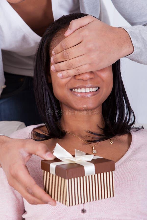 Mujer asombrosamente del hombre joven con la caja de regalo imágenes de archivo libres de regalías