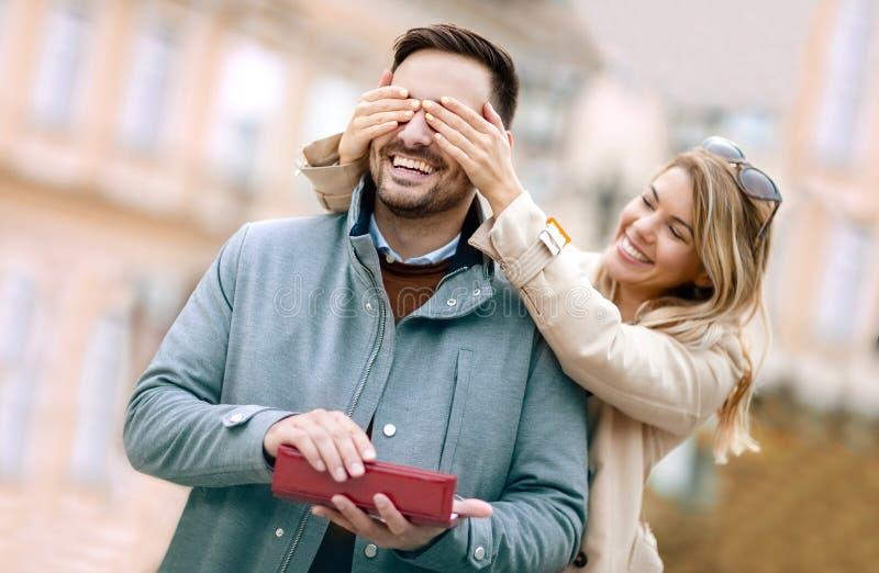 Mujer asombrosamente su novio con un regalo fotografía de archivo