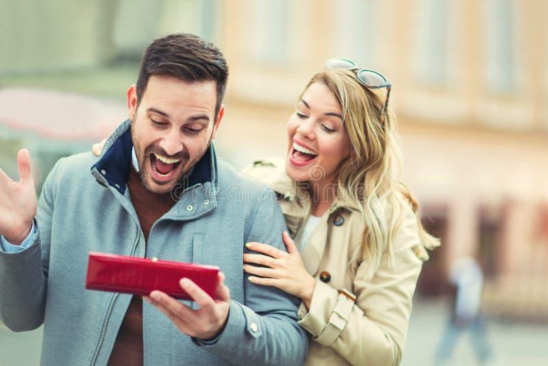 Mujer asombrosamente su novio con un regalo imagen de archivo