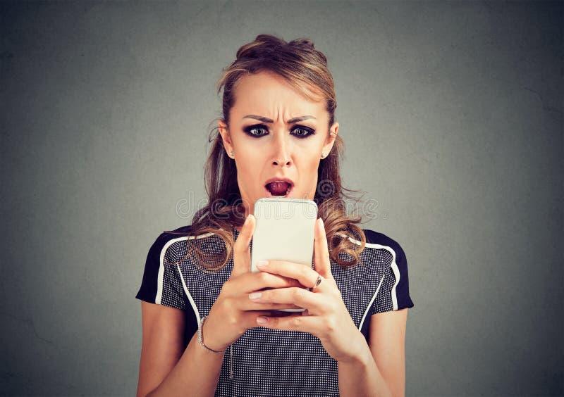 Mujer asustada chocada divertida que mira el teléfono que ve el mensaje de las fotos de las malas noticias con la emoción repugna fotografía de archivo libre de regalías