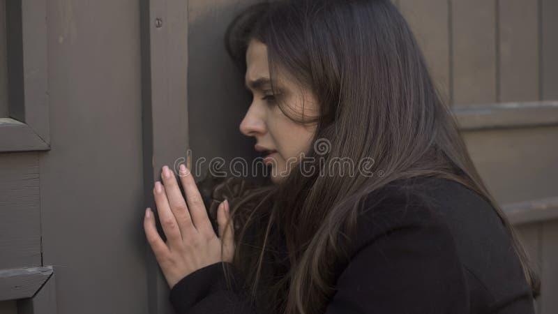 Mujer asustada que pide a la puerta abierta, perseguidora por el asesino enojado, riesgo del asesinato, horror fotografía de archivo