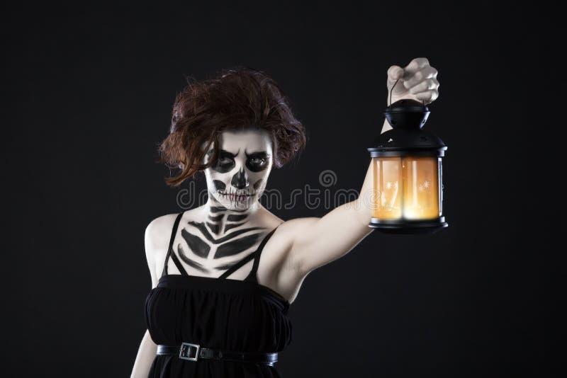 Mujer asustadiza con la linterna sobre el fondo negro - imagen fantasmagórica de una mujer asustadiza con los ojos oscuros y del  imagen de archivo libre de regalías