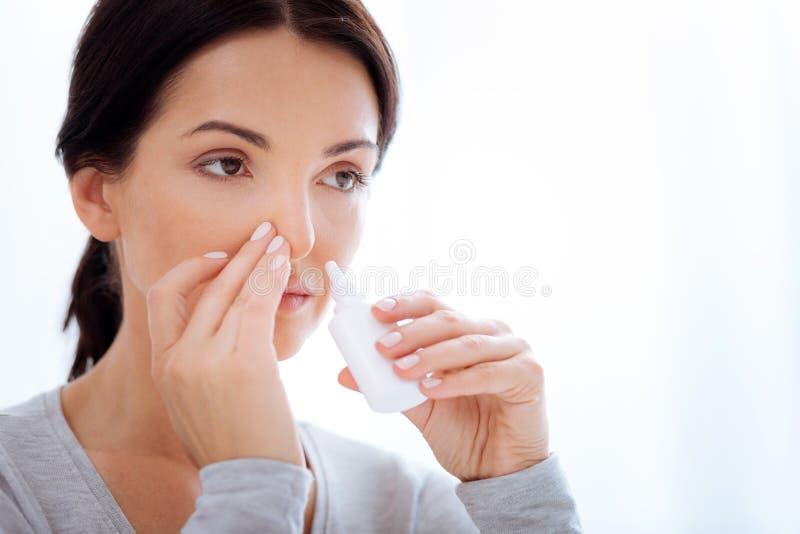 Mujer atenta que usa descensos nasales especiales fotos de archivo