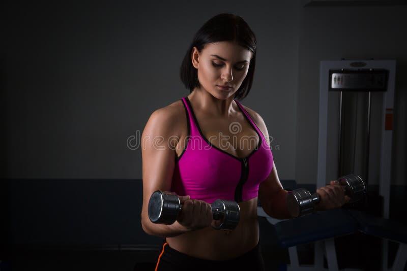 Mujer atlética brutal que bombea para arriba muscules con pesas de gimnasia fotos de archivo libres de regalías