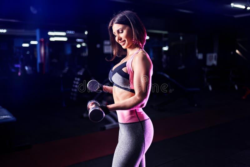 Mujer atlética brutal que bombea para arriba muscules con pesas de gimnasia foto de archivo