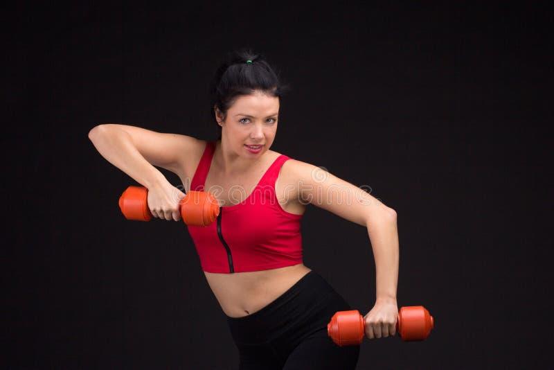 Mujer atlética brutal que bombea para arriba muscules con pesas de gimnasia fotografía de archivo libre de regalías