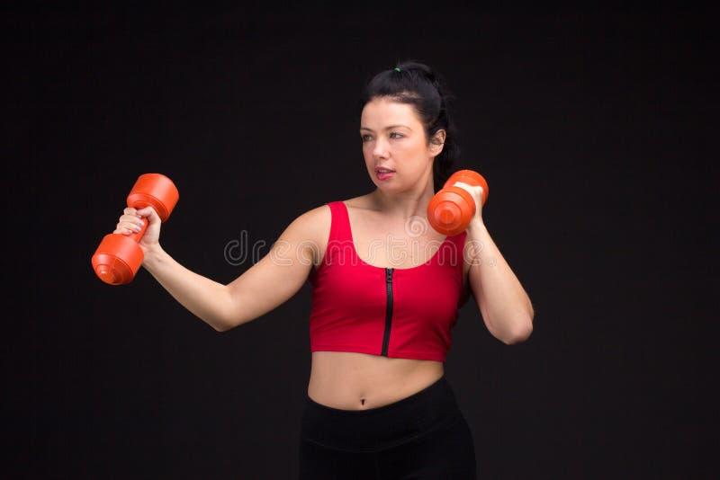 Mujer atlética brutal que bombea para arriba muscules con pesas de gimnasia foto de archivo libre de regalías