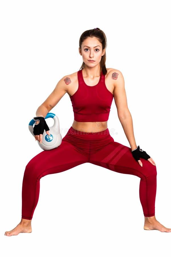 Mujer atlética con hacer del kettlebell estocadas Foto de la mujer aislada en el fondo blanco Fuerza - una imagen imagenes de archivo