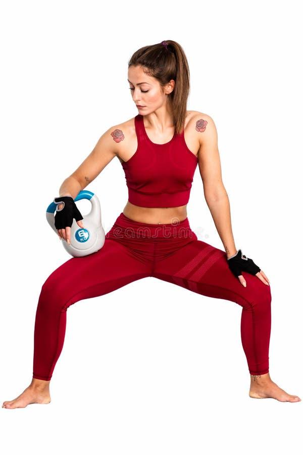 Mujer atlética con hacer del kettlebell estocadas Foto de la mujer aislada en el fondo blanco Fuerza - una imagen fotos de archivo