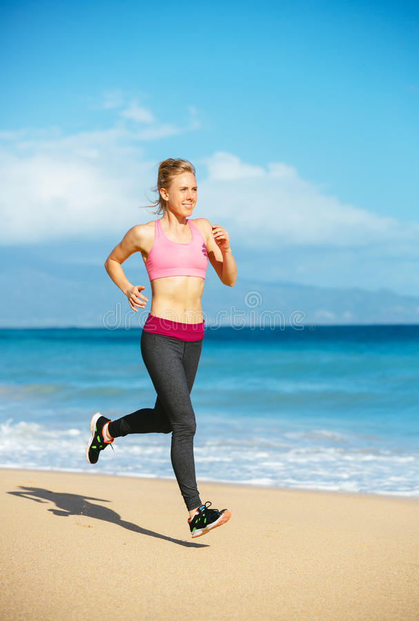 Mujer atlética de la aptitud que corre en la playa imágenes de archivo libres de regalías