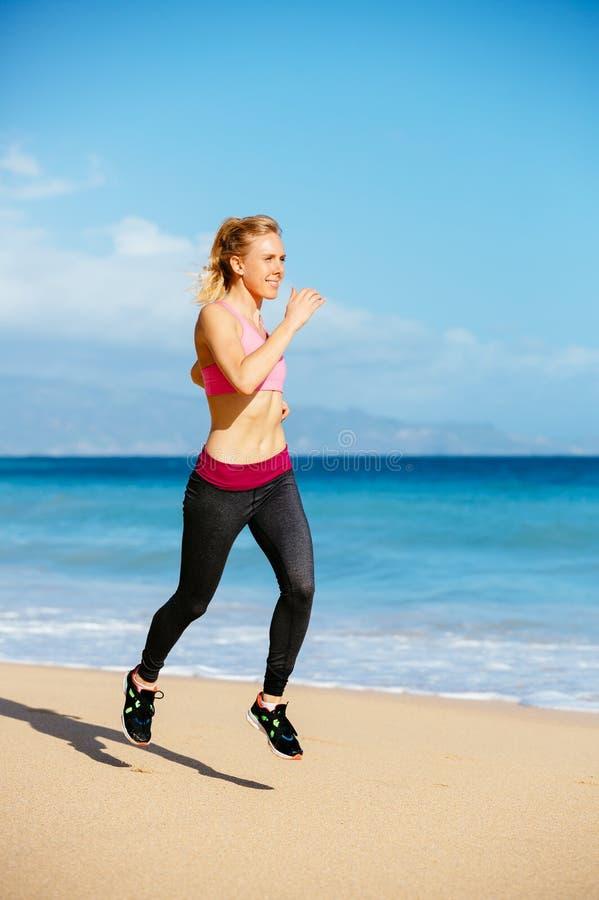 Mujer atlética de la aptitud que corre en la playa imagen de archivo