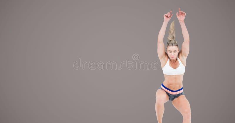 Mujer atlética de la aptitud que salta con el fondo marrón en blanco fotos de archivo libres de regalías