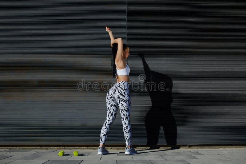 Mujer atlética de la visión trasera con la figura perfecta y las nalgas que estiran sus brazos fotografía de archivo